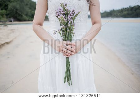 beautiful woman with white dress has holding a flower on the beach
