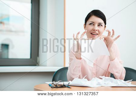 business woman sitting her desk getting rid of old papers with pleasure.