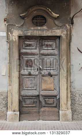 Ancient wood oak door with marble frame portal on old plaster wall Urbino Italy