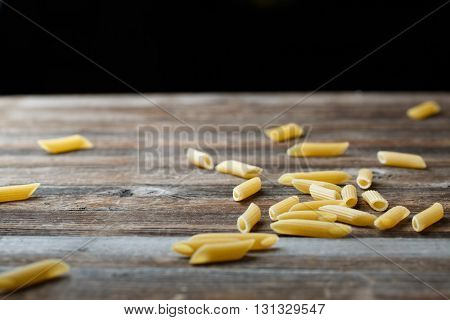 Falling penne pasta. Flying yellow raw macaroni over black background.