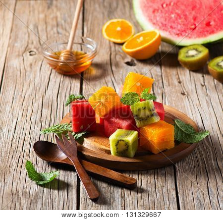 Colorful fruit salad (watermelon kiwi orange) with mint leaves on old wooden table.
