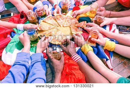 Many hands sharing pizza view from above - Multicultural sport fans arms on party table at cafe bar eating and drinking together - Concept of international friendship fun and sportive events meeting