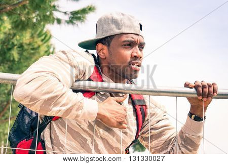 African man climbing wall border escaping from war and hunger - Young male crossing gate looking for peace and freedom - concept related to the phenomenon of emigration and humanitarian crisis