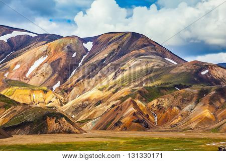 Multi-color picturesque rhyolitic mountains are lit with the sun. Travel to Iceland in the summer