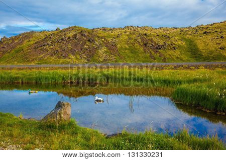 Small lake with thermal water. In the smooth surface of the water reflects the sky and clouds. Iceland in the summer