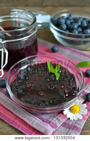 Blueberry jam in a glass jar on a wooden background