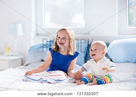 Little girl and baby boy brother and sister playing in parents bed. Family with children in the morning. Kids play in white bedroom. Nursery crib bedding and textile for young child. Siblings love.