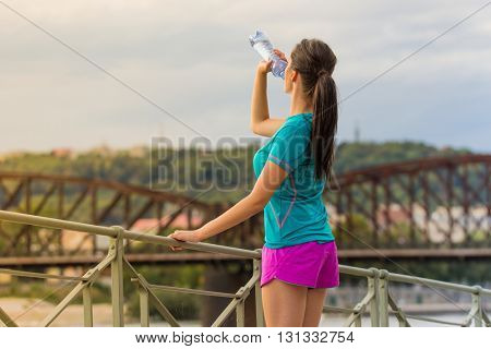 Young woman drinking water after running in the city. Female fitness model training outside in city,