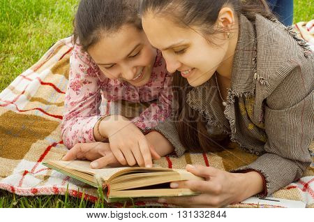 mother and daughter lying on the plaid and reading book
