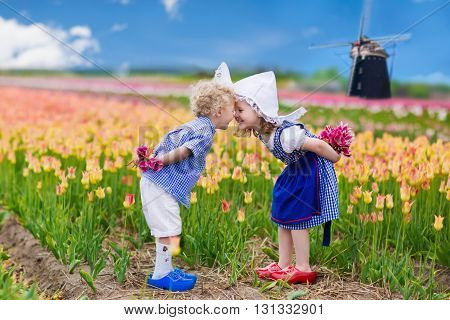 Happy Dutch children playing in blooming tulip flowers field. Boy and girl wearing traditional national costume wooden clogs and hat play with tulips next to a windmill in Holland Netherlands