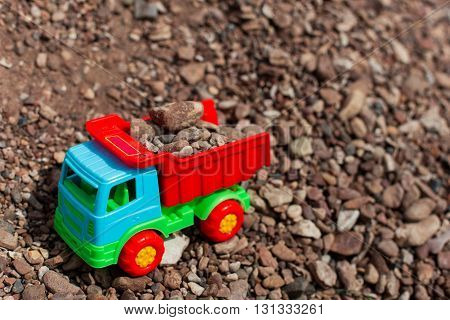 Children's toy colored small truck on the grass background of sand and stones loaded with cargo