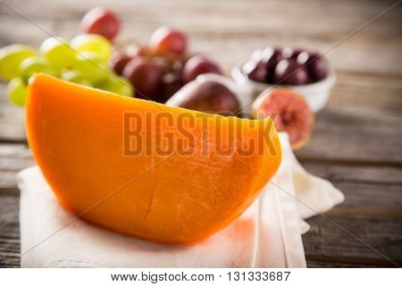 Delicious gouda cheese on old wooden table