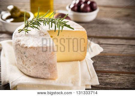 Delicious camembert cheese on old wooden table