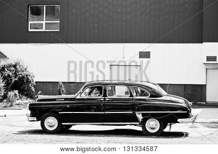 Podol, Ukraine - May 19, 2016: View Of Goes On Road Classic Car Gaz-12 Zim With Driver And Passenger
