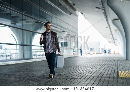 Full body portrait of a happy male traveler walking with bags and coffee.