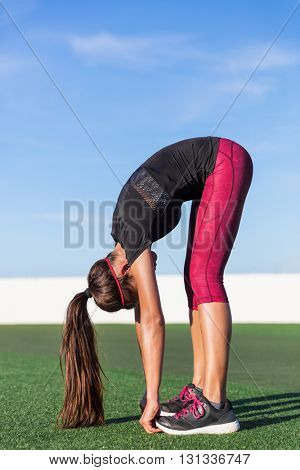 Standing forward bend yoga pose stretch fitness woman doing toe touch legs exercise. Girl stretching for lower back pain and flexibility by touching feet exercises in summer outdoors on grass park.