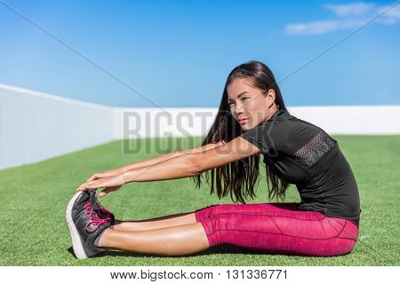 Fitness woman stretching hamstring leg muscles - back stretch sitting toe touch stretches. Seated forward bend. Sporty young athlete in activewear exercising flexibility on grass in sunny outdoor gym.
