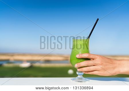 Woman holding green smoothie glass drinking fresh cold pressed organic vegetable spinach juice outside at cafe table. Healthy eating diet juicing cleanse detox. Unrecognizable person reaching for cup.