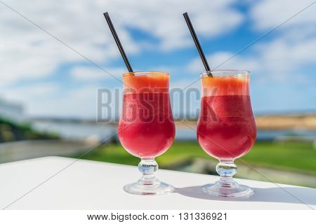 Healthy eating juice cleanse detox concept. Vegan diet juicing trend. Two glasses of red vegetable blend of carrot, beet juices glasses on outdoor cafe or restaurant table on summer sky background.
