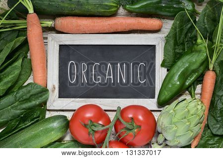 closeup of a chalkboard with the text organic placed on a pile of some different raw vegetables, such as cucumbers, tomatoes, carrots, artichokes, green peppers and zucchinis, on a rustic wooden table