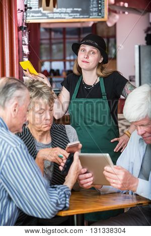 Frustrated Server Waiting On Customers With Electronics