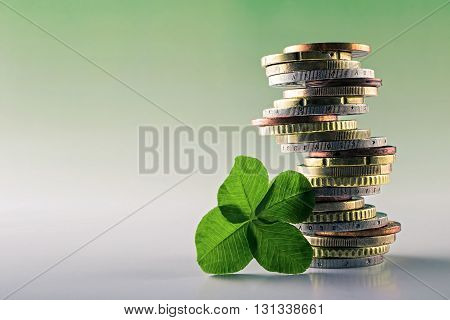 Euro money closeup coins,stacked on each other in different positions background green,Four Leaf Clover for luck.