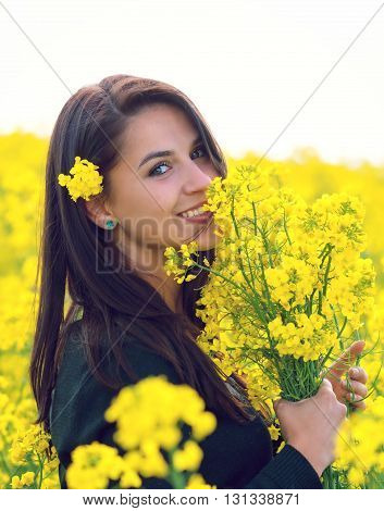 Beautiful Woman holding a bunch of rape flowers. Rape Field. Yellow Field. rapeseed plantation. Canola Field. Girl In Field.