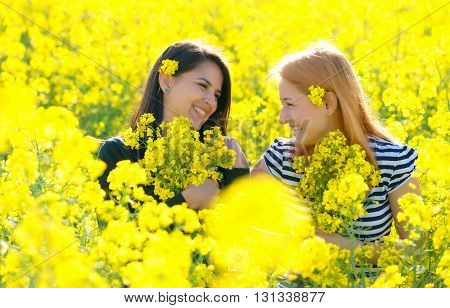 two beautiul girls having fun in the colza field