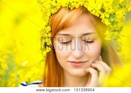 Portrait of woman with wreath of yellow flowers on the head.
