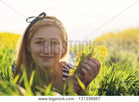 cute young girl in the middle of a field of yellow flowers