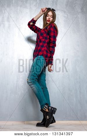 Beautiful Girl In Casual Clothes And Sunglasses Posing On Gray Concrete Wall. Active Lifestyle. Youth Fashion. Studio Shot