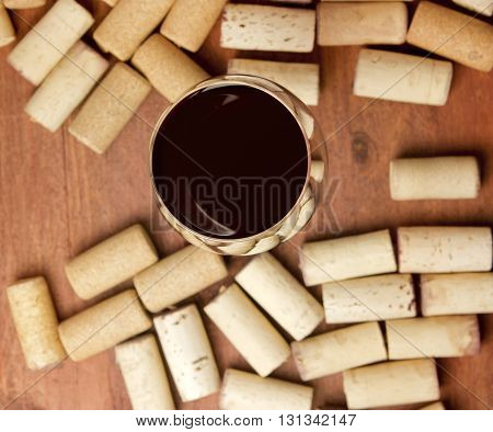A photo of a glass of red wine with defocused corks on wooden boards background texture around it