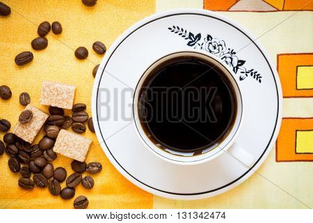 A cup of black coffee, brown sugar and coffee beans on a bright orange tablecloth