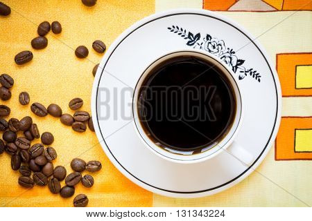 A cup of black coffee and coffee beans on a bright orange tablecloth