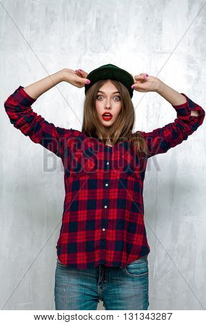 Beautiful Girl In Casual Clothes And Green Cap Posing On Gray Concrete Wall. Active Lifestyle. Youth Fashion. Studio Shot
