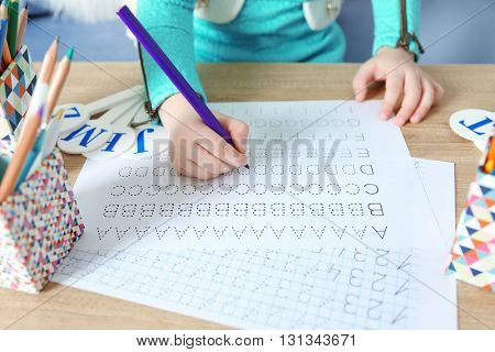 Little girl learning to write English letters at the table