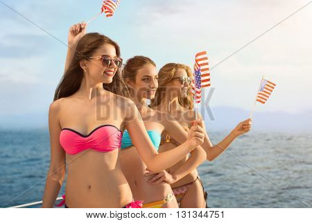 Smiling girls hold american flags. Attractive women on sea background. Greetings from USA. Happiness and freedom.