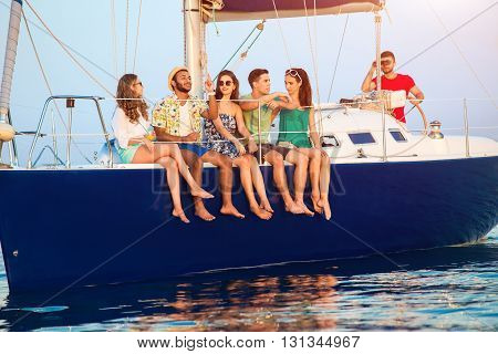 People sitting on a yacht. Young guys and girls smiling. Stories told by a friend. When we were young.