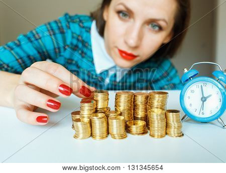 Saving woman stacking gold coins into columns