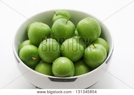 Fresh and green plums. Bowl of fresh green plums.