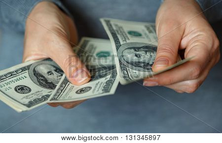 Woman counts the cash dollars in her hands