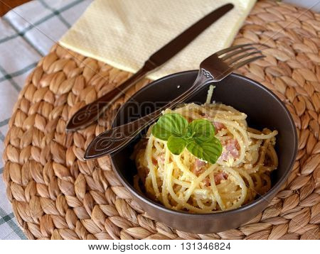 talian spaghetti Carbonara on a brown bowl on a table