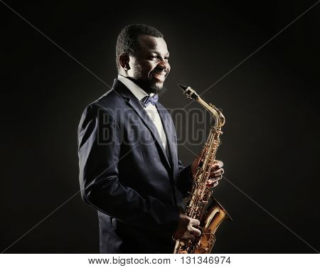 African American jazz musician playing the saxophone on grey background