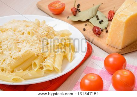 Penne pasta with grated cheese on a white round plate next to the spices and tomatoes on the table. Side view.