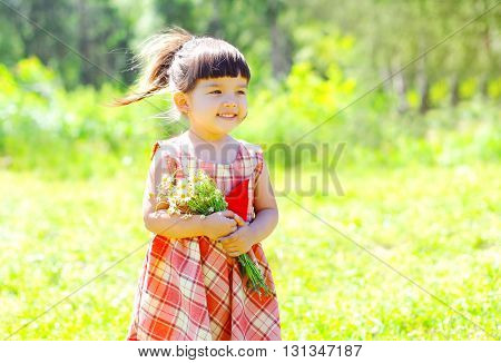 Portrait Happy Smiling Little Girl Child With Flowers In Summer Sunny Day