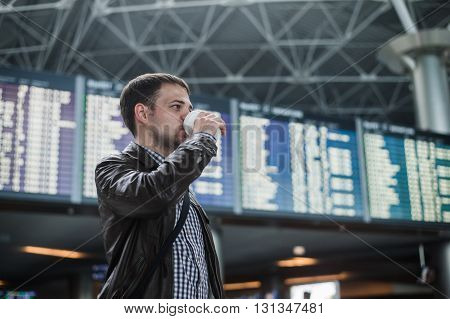 Young man in airport near flight timetable drinking coffee.