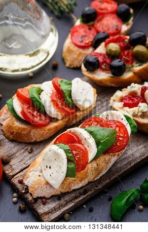Italian bruschetta with tomatoes, mozzarella cheese and herbs on a wooden board