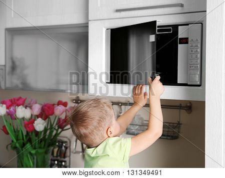 Little child playing with a microwave oven in the kitchen