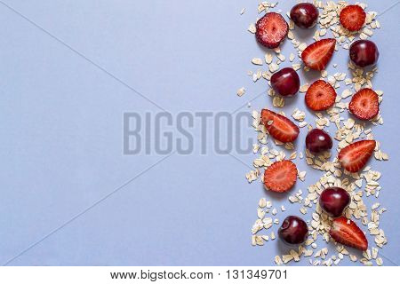 Concept of diet and healthy eating. Oat cereal with strawberries and cherries in border on a blue background with space for text. Top view
