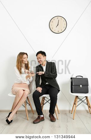 Man and woman waiting for interview indoors